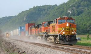 Orange locomotive hauling freight